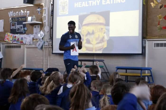 Darren Stephenson presenting at a school. He appears to be dancing in front of a cheeseburger, with an 'A' sign around his neck.