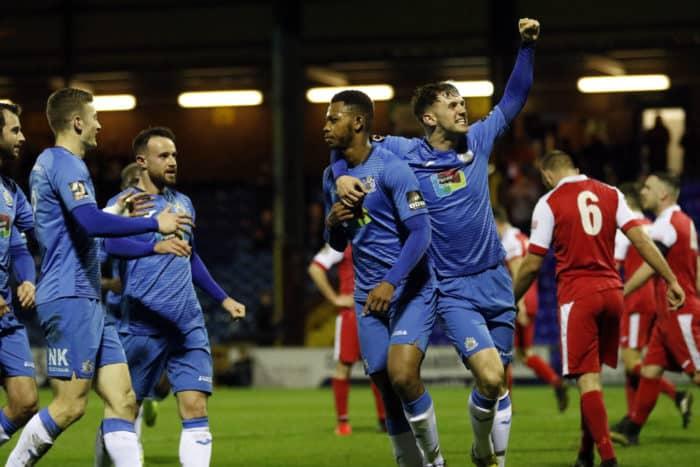 Jamie Stott, Matthew Warburton, Daniel Cowan, and Adam Thomas surrounding Nyal Bell, following his goal opening goal against Ashton United.