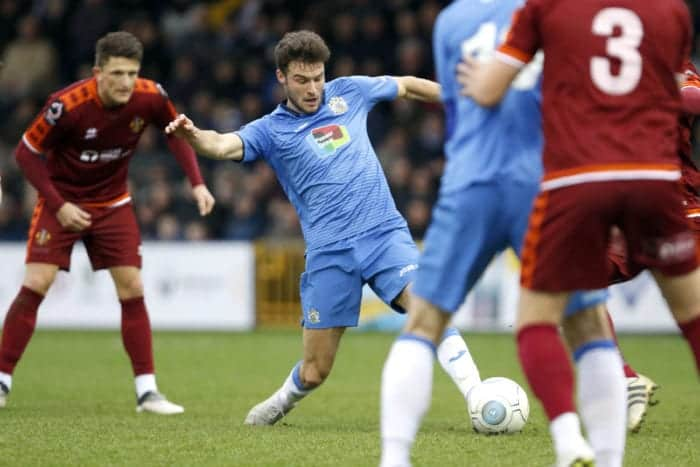 Jake Kirby challenges for the ball for Stockport County