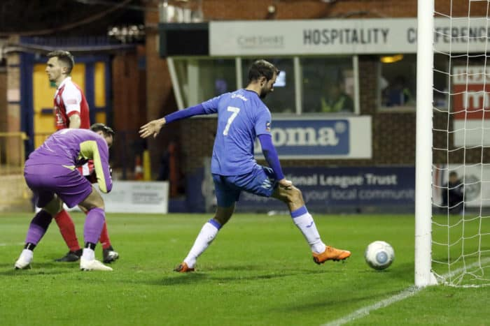 Adam Thomas taps the ball into the goal after Ashton United goalkeeper, Ollerenshaw, drops the ball.